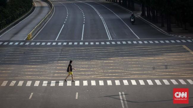 Pejalan kaki bisa menyeberang dengan sangat nyaman di kawasan MH Thamrin yang kosong, tak dicereweti klakson mobil dan motor yang biasanya tak memberikan ruang bagi para pejalan kaki. (CNNIndonesia/Safir Makki)