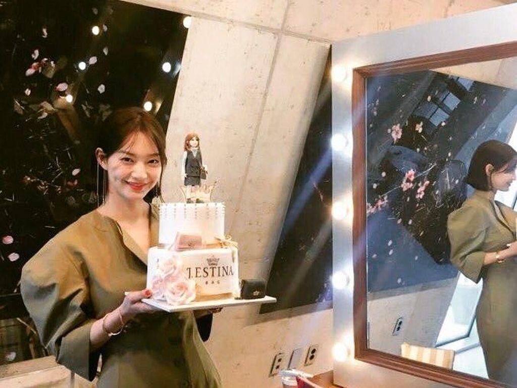 Uniknya cake yang dipegang oleh wanita 34 tahun ini bertingkat dengan bentuk karakter mirip Shin Min-a diatas kuenya. Foto: Instagram @illusomina