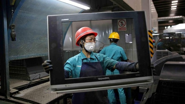 Para pekerja membuang televisi-televisi bekas di sebuah pabrik daur ulang di Neijiang, Provinsi Sichuan, China. (REUTERS/Stringer)