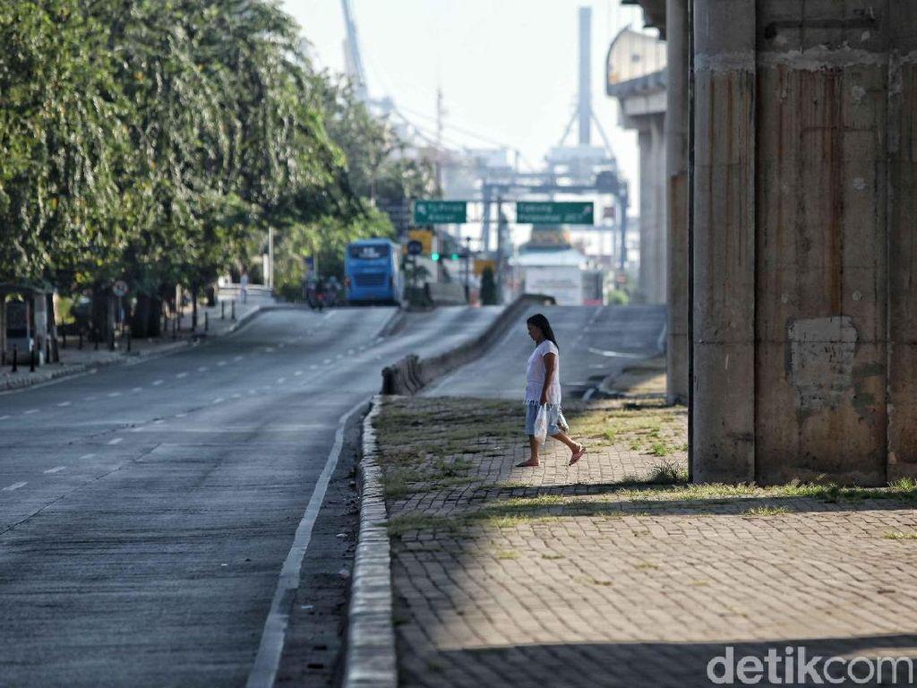 Seorang warga hendak menyebrang jalan dengan kondisi sepi dan lengang.