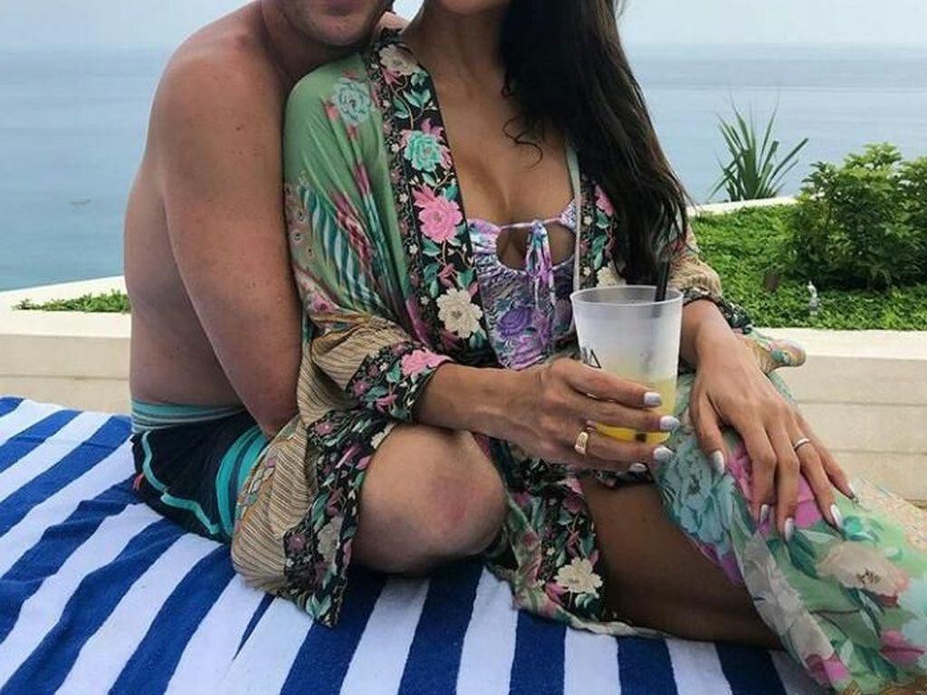Bersama dengan sang suami. Indah pun terlihat sedang asyik bersantai di pinggir pantai Bali. Sambil memegang minuman, kok keduanya makin romantis ya. Foto: Instagram @indahkalalo