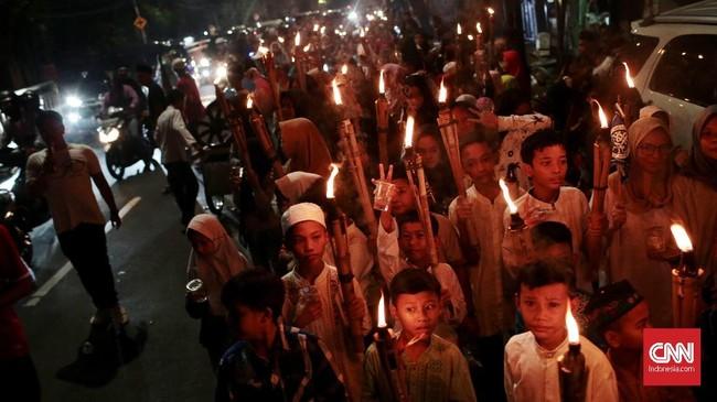 Warga Jakarta merayakan malam takbiran dengan pawai obor menyusuri jalan raya pada Kamis (14/6) untuk menyambut hari raya Idul Fitri 1439 Hijriyah. (CNN Indonesia/Andry Novelino)
