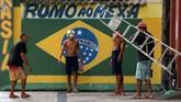 Para penduduk lokal bermain bola di dekat sebuah mural yang menggambarkan bendera Brasil di perkampungan Gloria di Rio de Janeiro. Tulisan di belakangnya adalah: