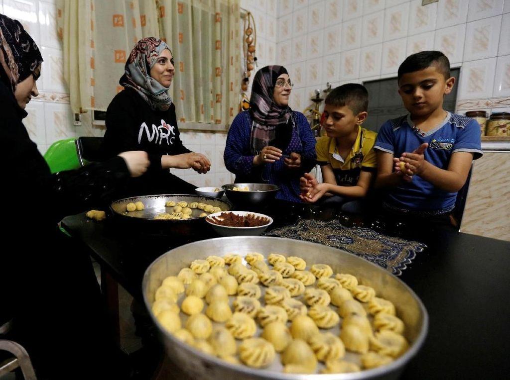 Sebuah keluarga di Yordania membuat kue dan makanan ringan tradisional lainnya untuk menyambut Hari Raya Idul Fitri. Muhammad Hamed/Reuters.