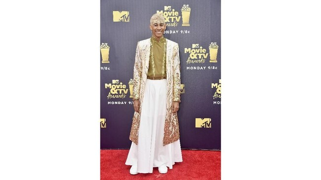 Aktor Keiynan Lonsdale memilih memakai busana berwarna putih dan kombinasi emas. Coat warna putih dan emas ini dipadukan dengan rok putih panjang dan tato emas di dahinya. (Frazer Harrison/Getty Images/AFP)
