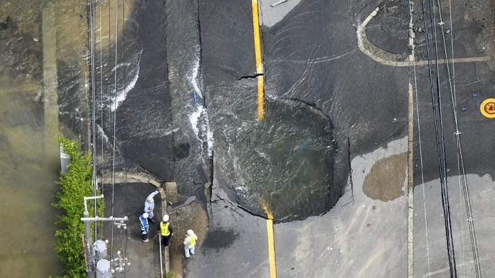 Water flows out from cracks in a road damaged by an earthquake in Takatsuki, Osaka prefecture, western Japan, in this photo taken by Kyodo June 18, 2018.   Mandatory credit Kyodo/via REUTERS ATTENTION EDITORS - THIS IMAGE WAS PROVIDED BY A THIRD PARTY. MANDATORY CREDIT. JAPAN OUT. NO COMMERCIAL OR EDITORIAL SALES IN JAPAN.