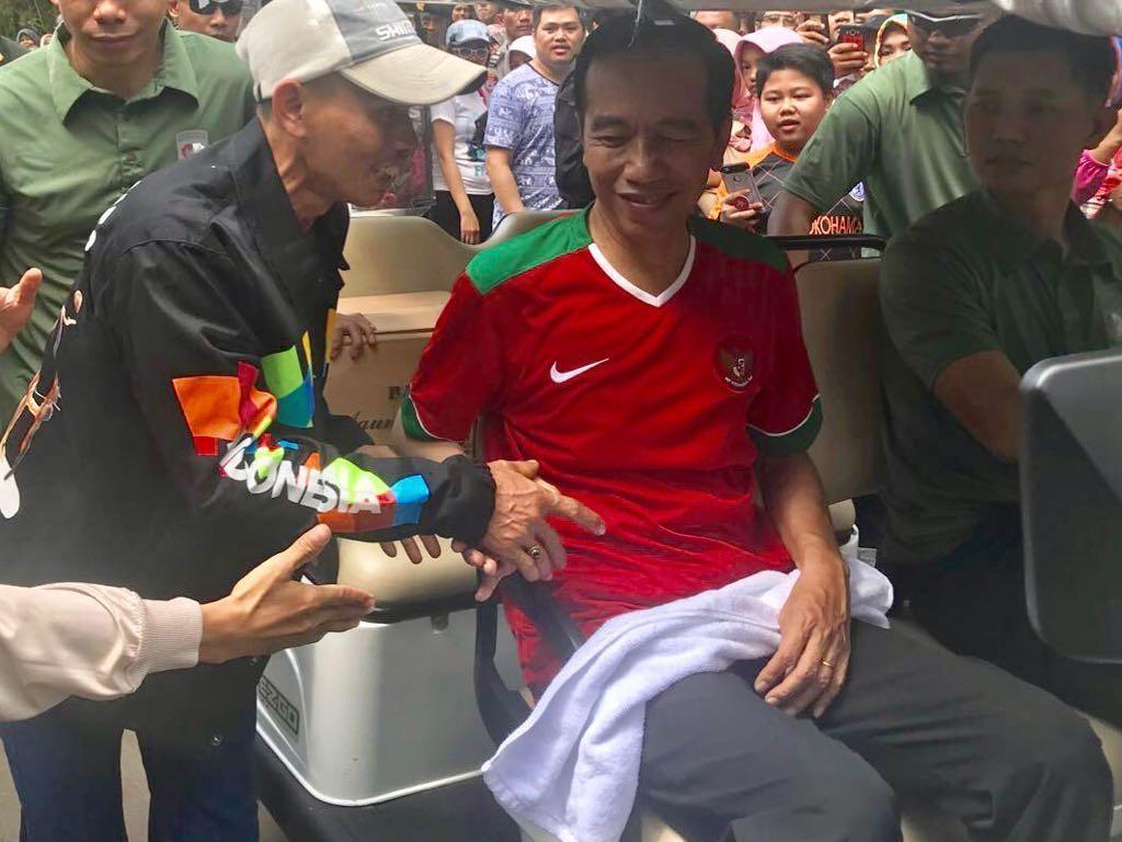 Seorang warga bernama Supriadin, menerimajaket yang dipakai Jokowi. Dia mengaku senang karena baru pertama kali datang ke Kebun Raya Bogor dan langsung bisa bertemu Jokowi. (Foto: Kris - Biro Pers Setpres)