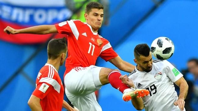 Pemain timnas Mesir,Mahmoud Hamdy berjibaku dengan Roman Zobnin dan Denis Cheryshev. Tak ada gol pada babak pertama laga Rusia vs Mesir. (REUTERS/Henry Romero)