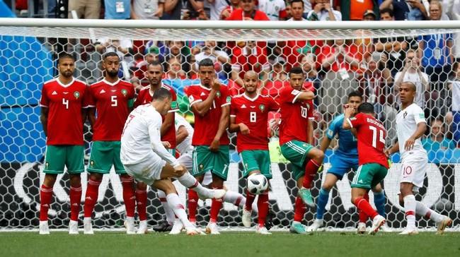 Cristiano Ronaldo berpeluang menggandakan keunggulan Portugal lewat tendangan bebas. Sayang tembakannya masih membentur pagar pertahanan Maroko. (REUTERS/Kai Pfaffenbach)