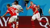 Pemain timnas Rusia Artem Dzyuba dan Roman Zobnin merayakan gol bunuh diri pemain Mesir, Ahmed Fathi, yang membuat tuan rumah memimpin 1-0. (REUTERS/Lee Smith)