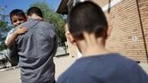 Imigran asal Salvador, Epigmenio Centeno, menggendong anaknya yang berusia tiga tahun Steven Atonay sementara putranya yang berusia 9 tahun, Axel Jaret, mengikuti. Epigmenio memutuskan tinggal di Meksiko setelah presiden AS Donald Trump mengeluarkan kebijakan kontroversial. (REUTERS/Jose Luis Gonzalez)