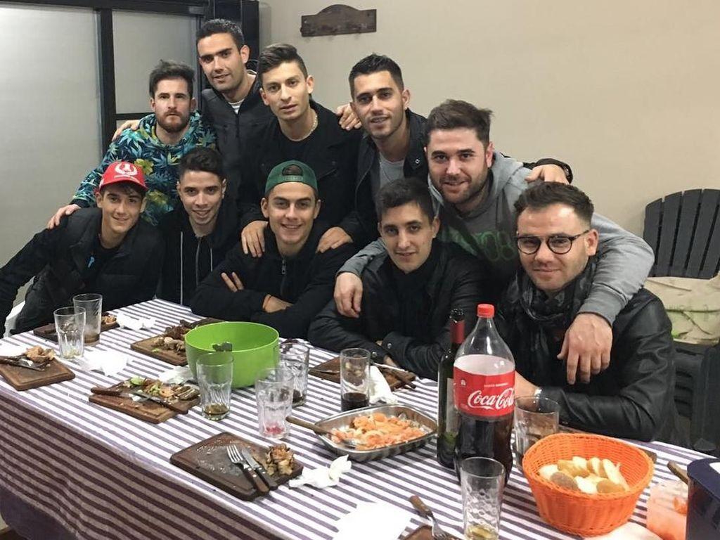 Dybala terlihat manis saat gaya bersama teman-temannya. Ada sebotol minuman soda besar di atas meja. Kira-kira apa ya santapan pilihan mereka? Foto: Instagram paulodybala