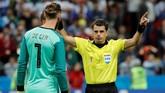 Di hadapan kiper Spanyol David De Gea, wasit Andres Cunha menunjukkan gestur bahwa kontroversi gol Iran akan dilihat di VAR. Usai menunggu beberapa saat, hasilnya gol Iran dianulir. (REUTERS/Toru Hanai)