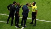 Pelatih Iran Carlos Queiroz (kedua dari kanan) mendapat arahan dari ofisial pertandingan di babak pertama. (REUTERS/John Sibley)
