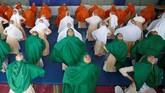 Sekumpulan murid perempuan Muslim di sebuah sekolah mempraktikkan yoga sebelum memulai kegiatan keseharian mereka. (REUTERS/Amit Dave)
