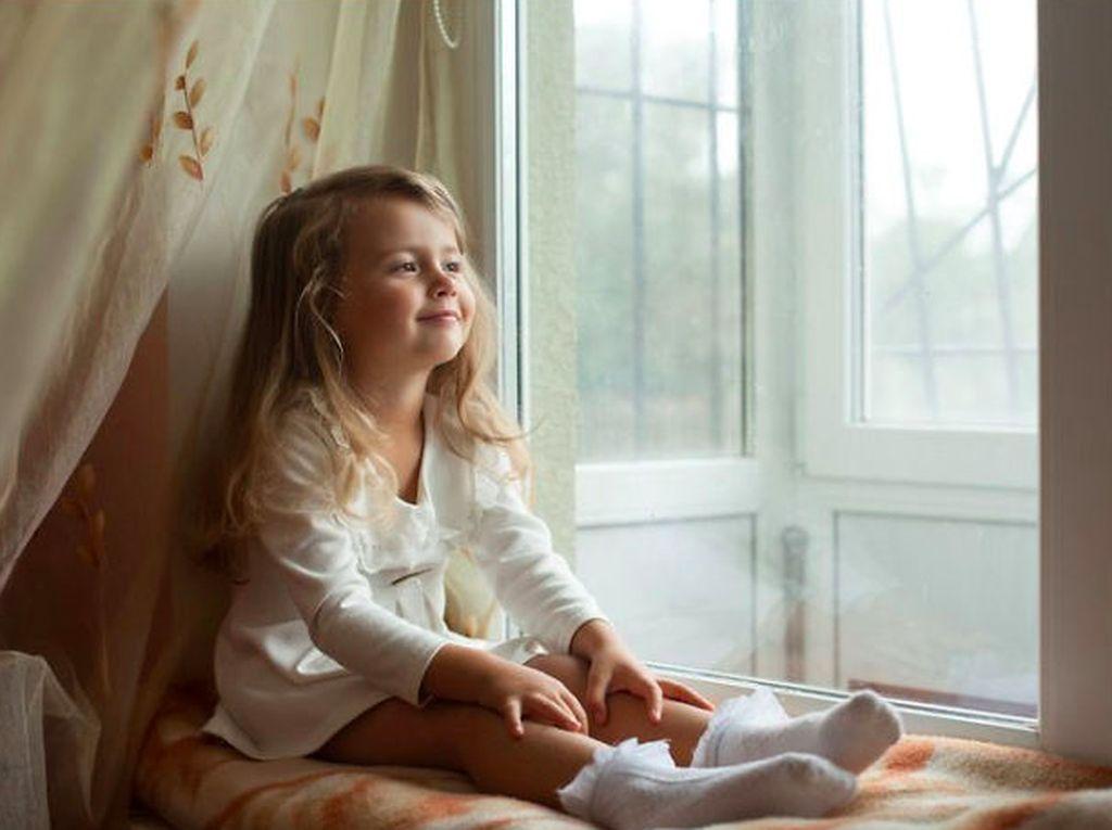 Foto seorang anak kecil di depan jendela. Foto: Brightside