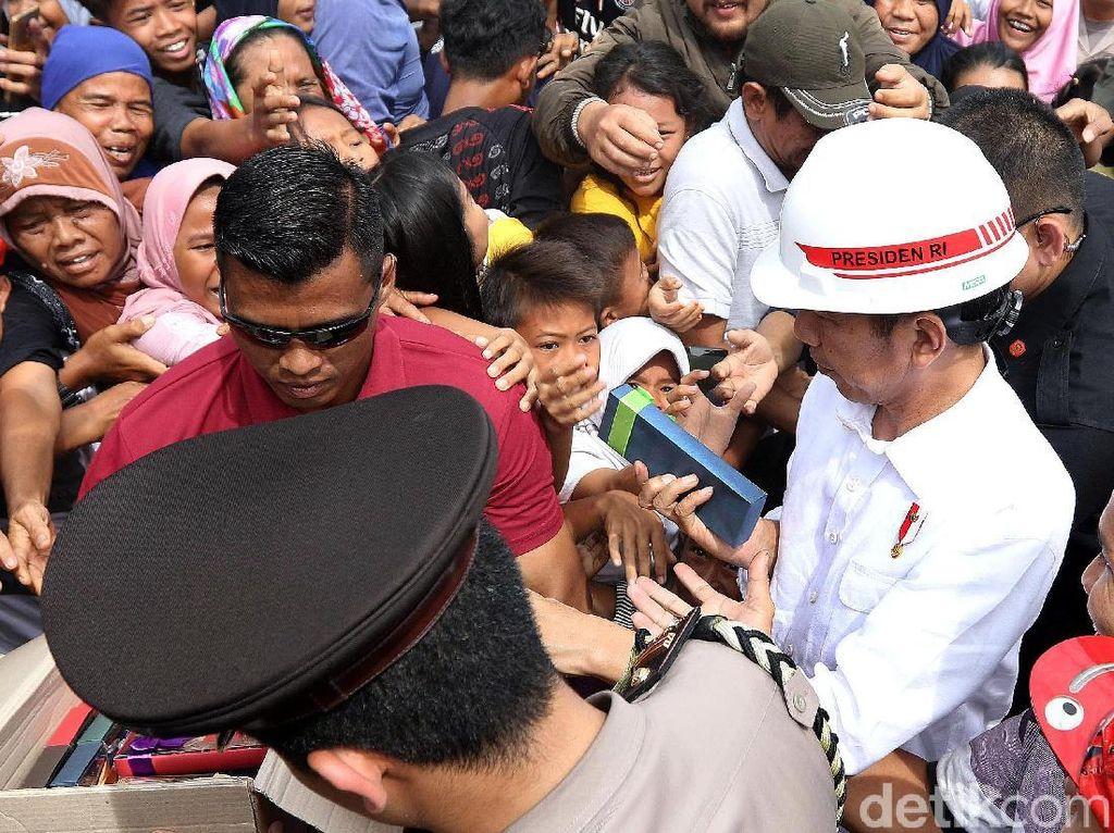 Jokowi juga membagikan kain batik dan buku.