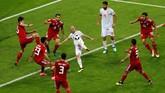Gelandang senior timnas Spanyol David Silva mendapat pengawalan dari enam pemain Iran. Silva hendak mencetak gol ke gawang Iran, sayang tendangannya masih melayang di atas mistar. (REUTERS/John Sibley)