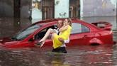 Seorang perempuan diselamatkan dari mobilnya yang terkena banjir di jalanan kota Nizhny Novgorod, Rusia. (Reuters/Murad Sezer)