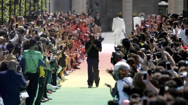 Usai peragaan, Virgil Abloh muncul dengan penuh emosional memberi salam pada penonton. Ia sempat memeluk mentor sekaligus rekan desainnya, Kanye West yang turut duduk di barisan depan. Lewat sambutan positif akan koleksinya ini, Abloh membuat sejarah baru akan karier menjanjikan di dunia mode. (REUTERS/Charles Platiau)