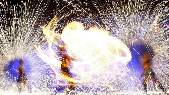 Para penari tampil dalam Festival Teater Api di sebuah museum berisi kerajinan-kerajinan tua di di Dudutki, Belarusia. (Reuters/Vasily Fedosenko)