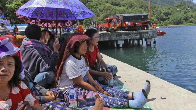 Ratusan keluarga korban tenggelamnnya KM Sinar Bangunbedatangan ke dermaga Pelabuhan Tigaras, Danau Toba, Sumatera Utara, Jumat (22/6). (dok. ANTARA FOTO/Irsan Mulyadi)
