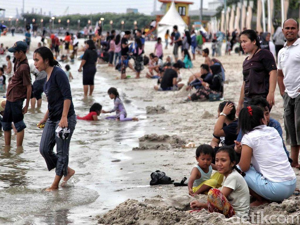 Sejumlah warga bermain air di Pantai Lagoon, Ancol, Jakarta Utara, Sabtu (23/6).