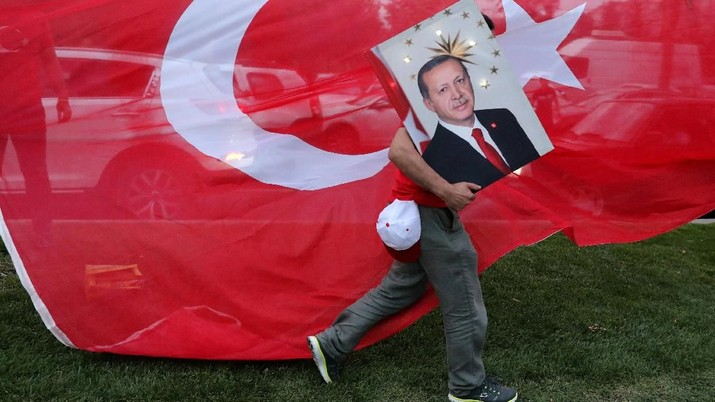 A supporters of Turkish President Tayyip Erdogan holds his picture in front of a Turkish flag, in front of Turkey's ruling AK Party (AKP) headquarters in Istanbul,Turkey, June 24, 2018. REUTERS/Goran Tomasevic      TPX IMAGES OF THE DAY