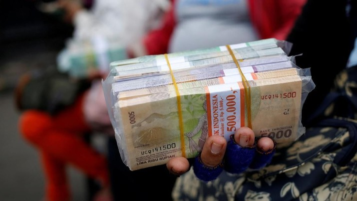 FILE PHOTO: A woman who makes change for large bank notes sits beside stacks of Indonesian Rupiah notes in a street in Jakarta, Indonesia  April 27, 2018. REUTERS/Willy Kurniawan/File Photo                  GLOBAL BUSINESS WEEK AHEAD