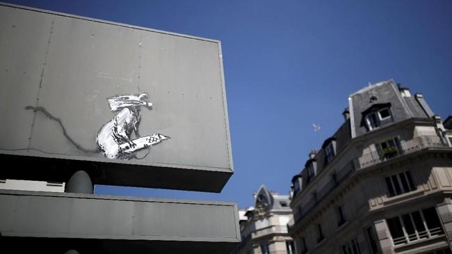 Soal siapa Banksy pun hingga kini masih misterius. Banyak yang percaya ia adalah Robert Del Naja. Musisi 52 tahun itu bermain di Lyon, Prancis, Minggu (24/6). Karya Banksy sendiri bisa terjual lebih dari US$1 juta (sekitar Rp14 miliar). (REUTERS/Benoit Tessier)