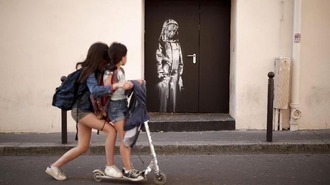 Di seri kedelapan, Banksy membuat mural perempuan berduka. Banyak kalangan menganggap mural yang digambar di dinding dekat dengan pintu keluar darurat Bataclan itu sebagai tanda perpisahan menyedihkan sang seniman terhadap Paris. (REUTERS/Benoit Tessier)