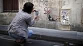 """Salah satu karya ikonis Banksy adalah gambar tikus got yang duduk di bawah tulisan """"Mei 1968"""" yang legendaris, mengenakan pita Minnie Mouse. Taman bermain Disneyland yang terletak di luar ibu kota Prancis menjadi salah satu perusahaan dengan pekerja terbanyak. (REUTERS/Benoit Tessier)"""