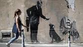 Mural seri keempat menyiratkan kritik terkait kapitalisme. Seorang pebisnis mengenakan jas hitam menawarkan tulang kepada seekor anjing yang salah satu kakinya telah digergaji dahulu oleh pebisnis itu. (REUTERS/Benoit Tessier)