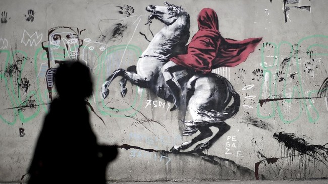 Coretan mural terbaru seniman Banksy terlihat di Prancis. Karya ini mengkritik pemerintah negara itu soal pelarangan pemakaian niqab. Mural itu menunjukkan Napoleon yang mengenakan hijab merah seraya menunggangi kuda putihnya yang melintasi Gunung Alpen untuk menyerang Italia pada 1800. (REUTERS/Benoit Tessier)
