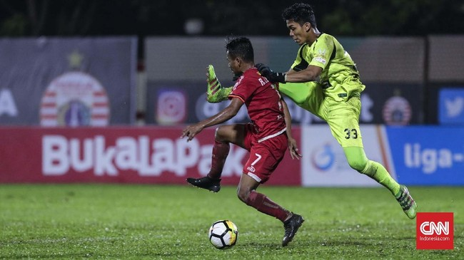 Penjaga gawang Persebaya Miswar Saputra harus ke luar sarang untuk menghalau serangan Persija melalui kaki Ramdani Lestaluhu. (CNNIndonesia/Adhi Wicaksono)
