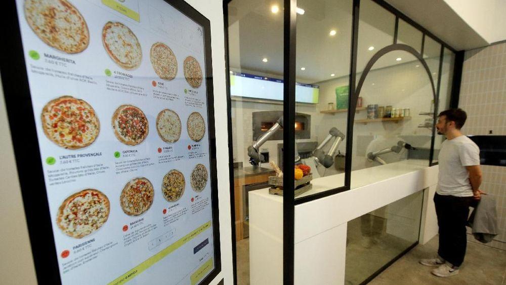 Pengunjung melihat proses robot pizzaiolo menyiapkan pizza diruang display startup Prancis EKIM di Montevrain Paris, Prancis, 26 Juni 2018. REUTERS / Philippe Wojazer
