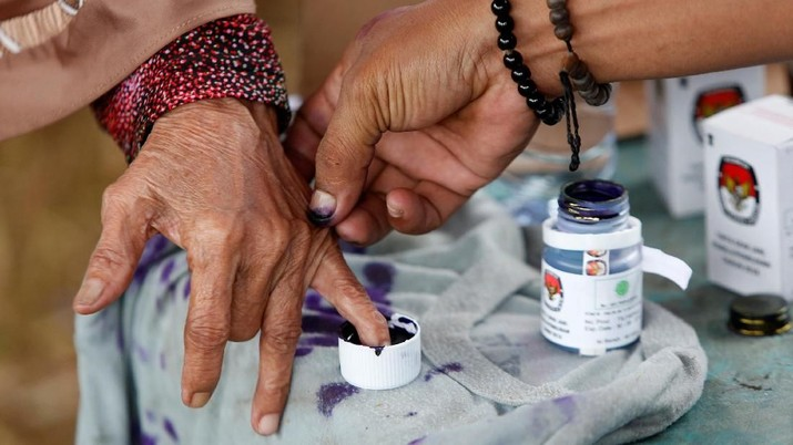 An election official helps an elderly woman to mark her finger with ink after casting her vote during regional elections in Tangerang, west of Jakarta, Indonesia June 27, 2018. REUTERS/Willy Kurniawan