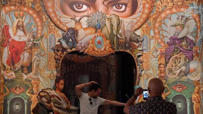 Pengunjung mengambil foto di depan karya 'Detail of the King of Pop' dari Mark Ryden yang terpajang di pameran Michael Jackson:On The Wall'. (REUTERS/Toby Melville)