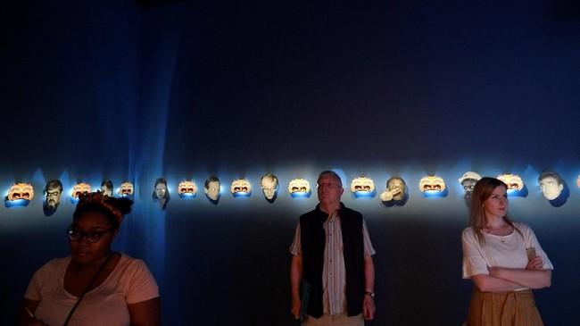 Pengunjung menyaksikan karya Dan Mihaltianu yang bertajuk The Last Days of Michael Jackson in Bucharest'.(REUTERS/Toby Melville)