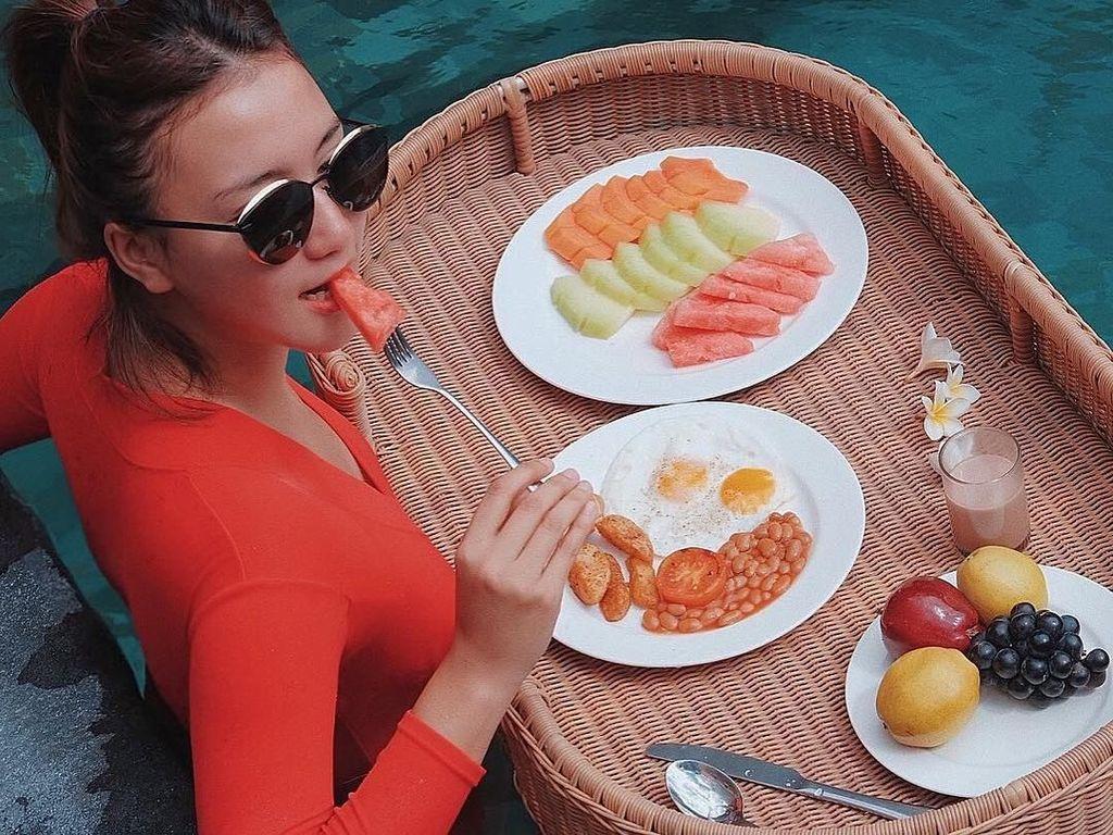 Yummy! Erica tampak sedang asyik menikmati menu sarapannya. Ia sarapan dengan tema floating breakfast yakni makan sambil berenang. Seru banget ya?Foto: Instagram ericaputrii