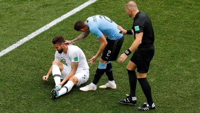 Striker timnas Prancis Olivier Giroud (kiri) terduduk di lapangan usai berduel dengan pemain Uruguay. Di Piala Dunia 2018 Giroud sudah tampillima kali namun belum juga mencetak gol. (REUTERS/Carlos Barria)