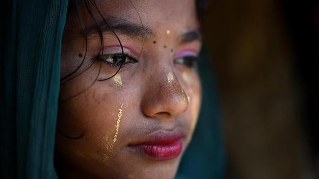 Berbeda dengan biasanya, pengungsi Rohingya punya cara khusus untuk menghalau sinar matahari ke kulitnya.(REUTERS/Clodagh Kilcoyne)