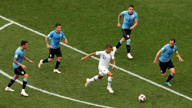 Striker muda Prancis Kylian Mbappe mendapat kawalan dari empat pemain Uruguay. Sejauh ini Mbappe sudah mencetak tiga gol dan memberikan satu assist di Piala Dunia 2018. (REUTERS/Carlos Barria)