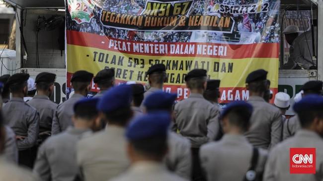 Selain mengawal aksi, aparat kepolisian juga mengatur arus lalu lintas di ruas jalan yang terpantau padat. Sejumlah kendaraan bermotor diperbolehkan melintas di Jalan Medan Merdeka Timur.(CNN Indonesia/Adhi Wicaksono)