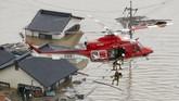 Aksi tim penyelamat mengevakuasi korban banjir bandang di Kurashiki. Rumahnya terendam hingga tersisa bagian atap. Petugas harus menggunakan helikopter untuk menyelamatkan korban. (Kyodo/via REUTERS).