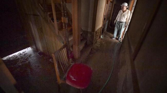 Seorang pria melihat rumahnya yang rusak oleh hujan lebat di Soja, prefektur Okayama. (Kyodo/via REUTERS).