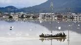 Masyarakat banyak yang masih terjebak di rumah mereka, mengingat kesulitanmengevakuasikan diri akibat air bah yang kadung menyerang. (Kyodo/via REUTERS).