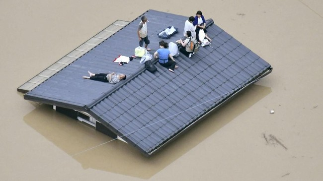 Bagi warga yang rumahnya terendam seperti di Kurashiki ini, atap menjadi satu-satunya area bebas banjir. Mereka pun menunggu pertolongan tim. (Kyodo/via REUTERS).