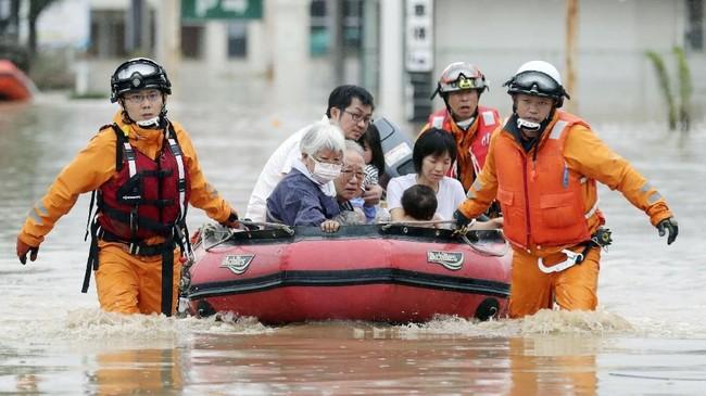 Tim penyelamat juga mengevakuasi warga Jepang korban banjir bandang dengan perahu, bagidaerah yang belum terendam tinggi. (Kyodo/via REUTERS).
