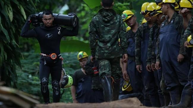 Seorang menyelam memanggul tangki oksigen keluar dari Gua Tham Luang, dimana 12 remaja dan pelatih sepak bolanya terjebak selama dua pekan terakhir.(REUTERS/Athit Perawongmetha)